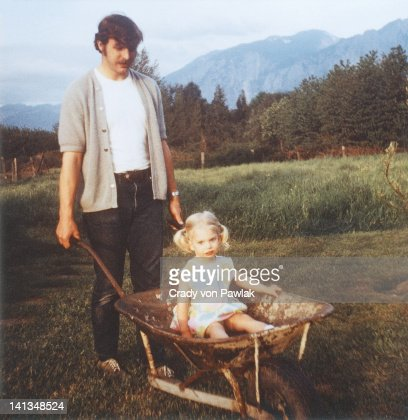 Father giving daughter wheelbarrow ride