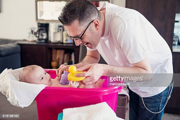 Padre dando un su bebé niña un baño en una mesa de cocina.
