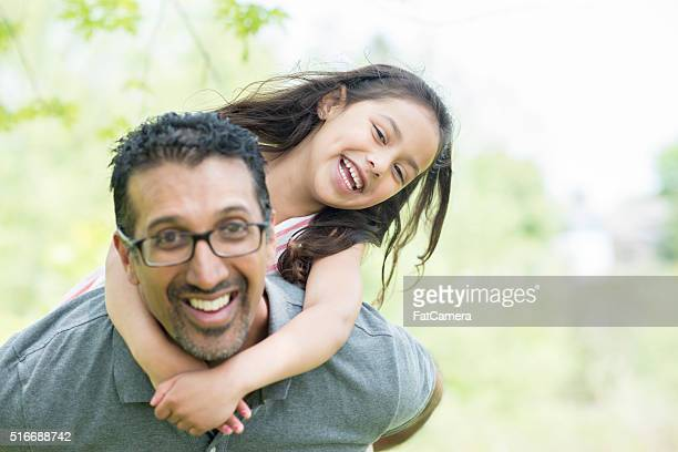 Father Giving His Daughter a Piggy Back Ride