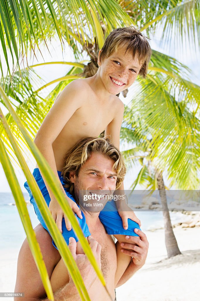 Father giving his son (10-12) piggy back ride : Stock Photo