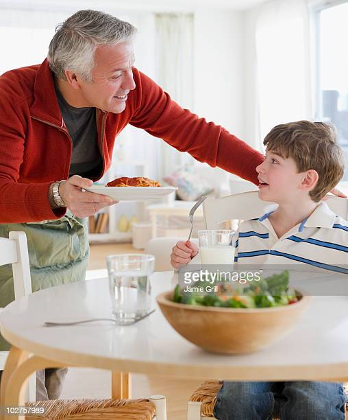 Father giving plate of spaghetti to son
