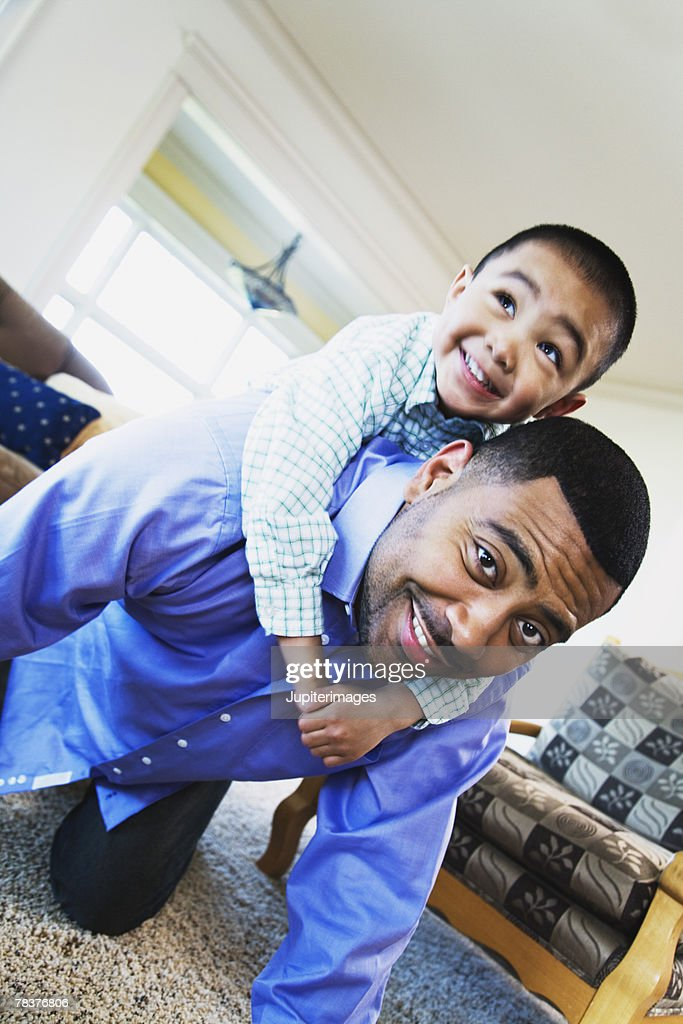 Father giving son piggyback ride : Stock Photo