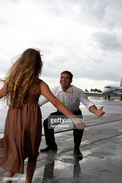 Father greeting daughter (6-8) on airport runway, smiling