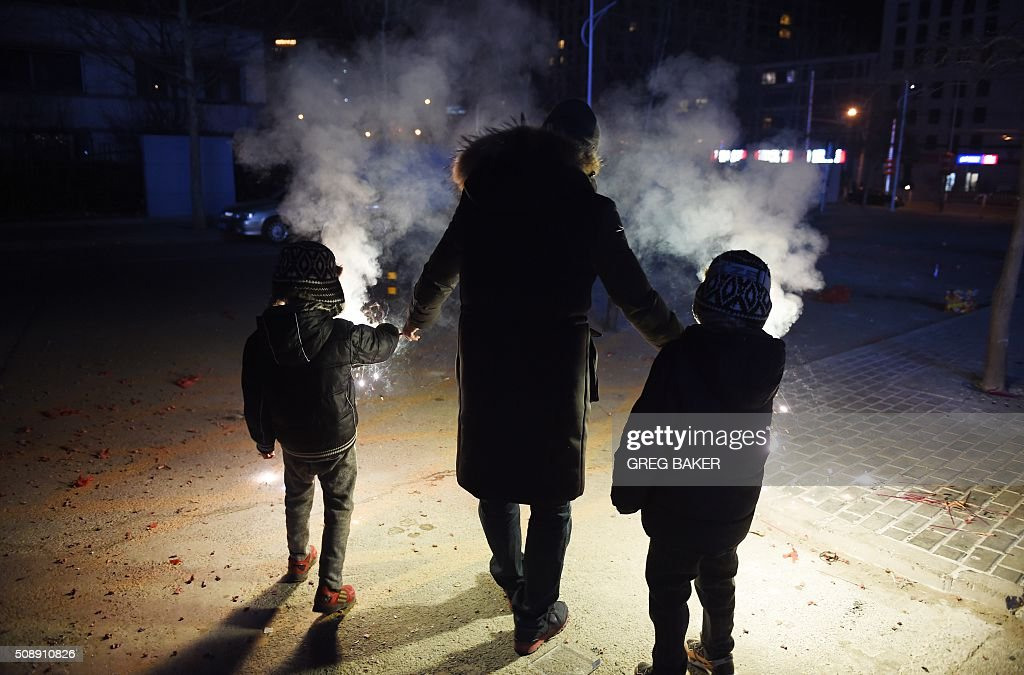 A father guides his sons as they light fireworks on a street in Beijing on February 7, 2016, the eve of the Lunar New Year. China marks the beginning of the Lunar New Year, the Year of the Monkey, on February 8. AFP PHOTO / GREG BAKER / AFP / GREG BAKER