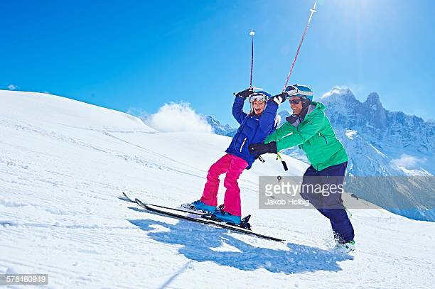 Father guiding daughter to ski, Chamonix, France