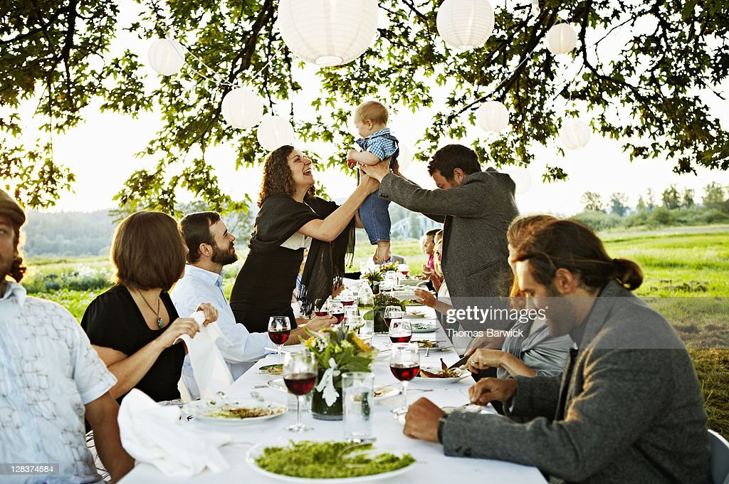 Father handing baby to friend across table : Stock Photo