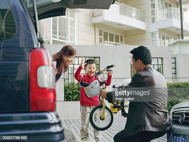 Father handing new bicycle to son (4-6), mother watching