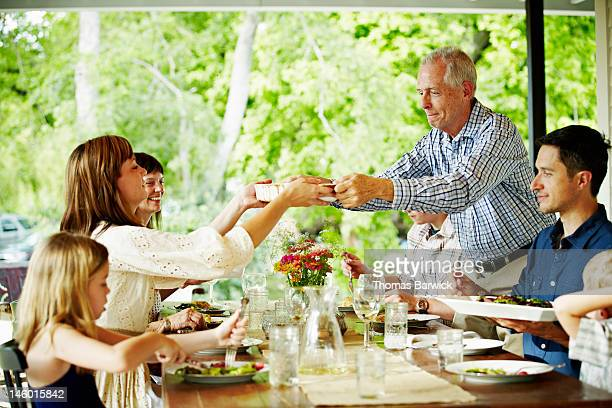 Father handing plate of food across table