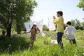 Father hanging laundry, children (8-9) running around