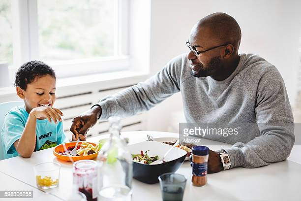 Father having food with son at dining table in house