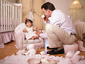 Father having tea party with baby girl (9-12 months)
