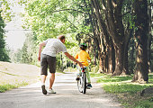 Father help his son ride a bicycle