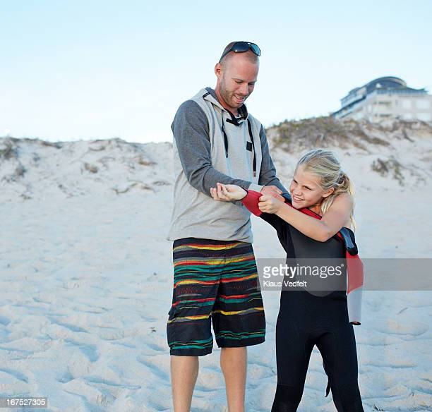 Father helping child with wetsuit