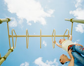 Father helping daughter across monkey bars, low angle view