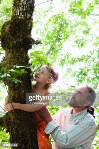Father helping daughter climb tree : Stock Photo