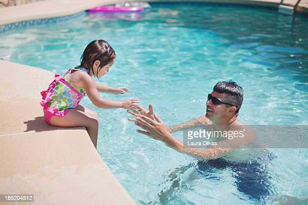 Father helping daughter det into swimming pool