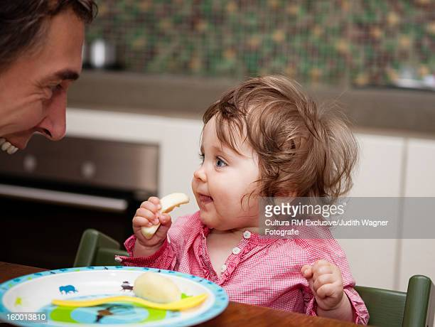 Father helping daughter eat at table