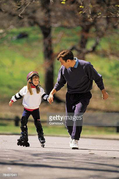 Father helping daughter on inline skates