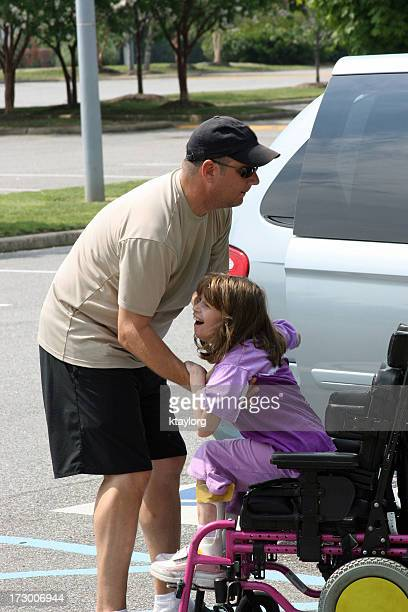 Father helping daughter out of wheelchair