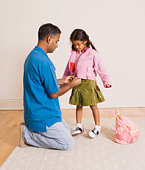 Father helping daughter put on jacket