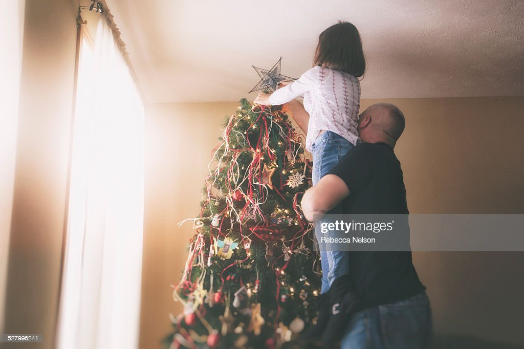 father helping daughter put star on Christmas tree : Stock Photo
