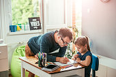 Father helping daughter to finish homework in her room