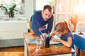 Father lean on the desk next to daughter helping her to finish homework