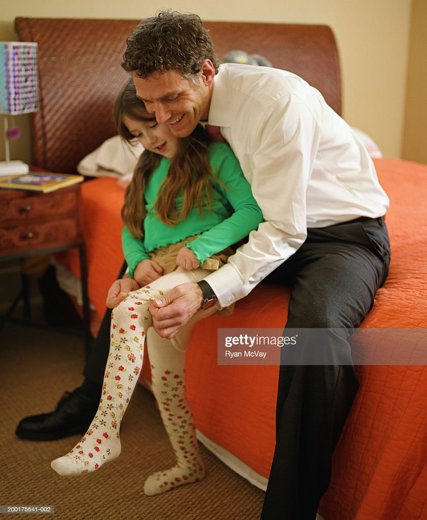 Short Father Daughter Dance Songs: Father Helping Daughter To Put On Tights Stock Photo