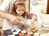Father helping daughter with cake mixture