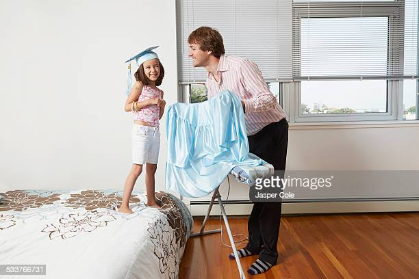Father helping daughter with graduation robes