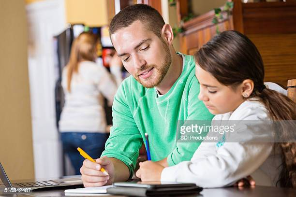 Père aider sa fille à faire ses devoirs dans la cuisine de famille