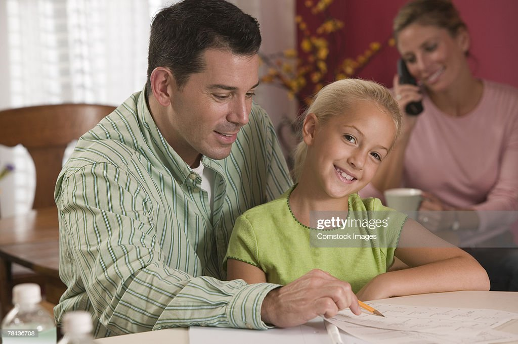 Father helping daughter with homework : Stock Photo