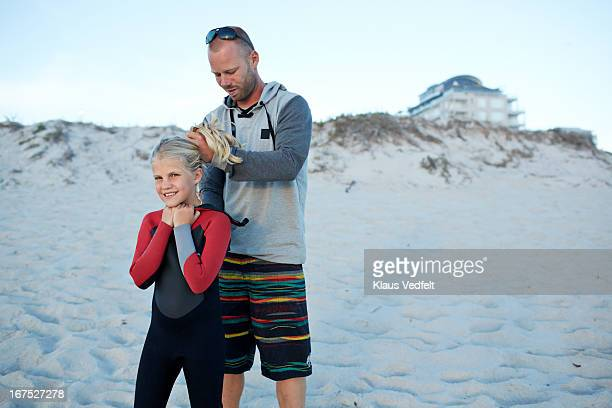 Father helping daughter with wetsuit