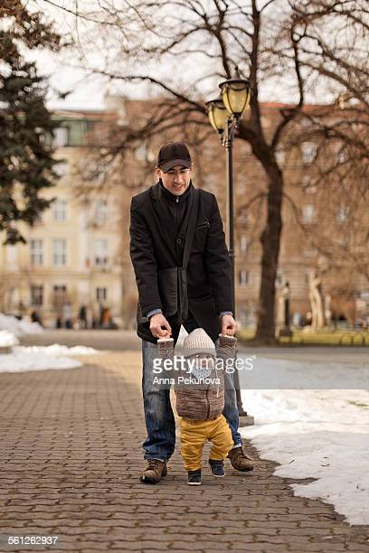 Father helping his baby boy learning to walk