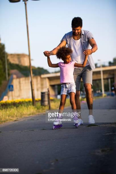 Vater seiner Tochter beim Rollschuhlaufen bei Sonnenuntergang zu helfen.