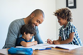 Young black father helping his boys with homework. Multiethnic brothers studying with their dad at home. Two cute children doing homeworks with the help of their loving parent.