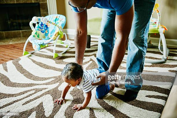 Father helping infant son crawl on floor in home
