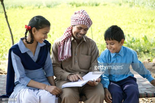 Father helping school children to study