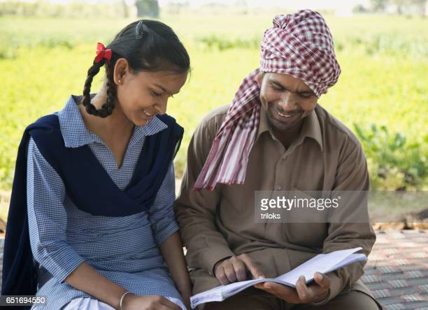 Father helping schoolgirl to study