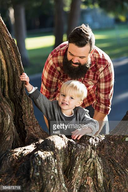 Father helping son climb tree