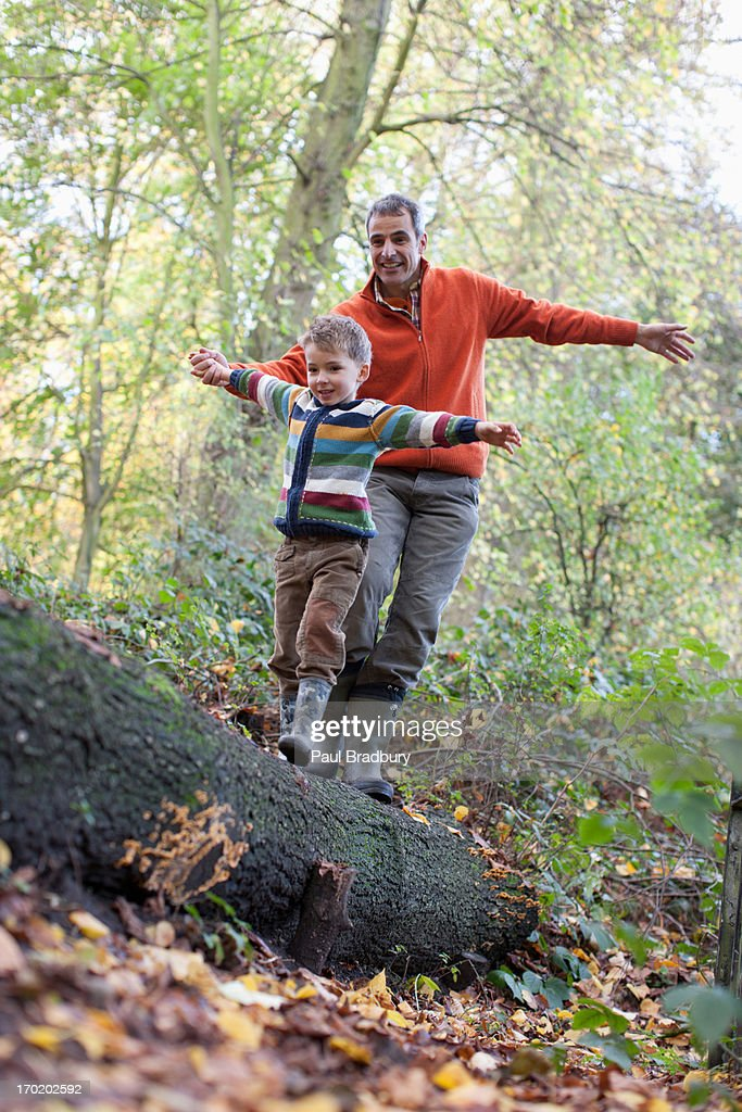 Father helping son cross log outdoors : Stock Photo