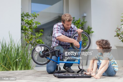 Father helping son fix bicycle