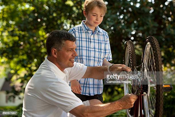 father helping son fix bike