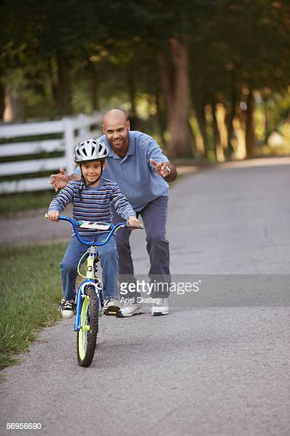 Father helping son learn how to ride bike