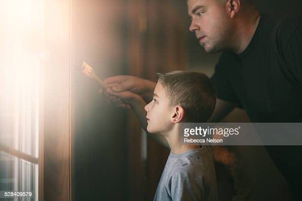 father helping son paint