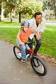 Father helping son ride bicycle