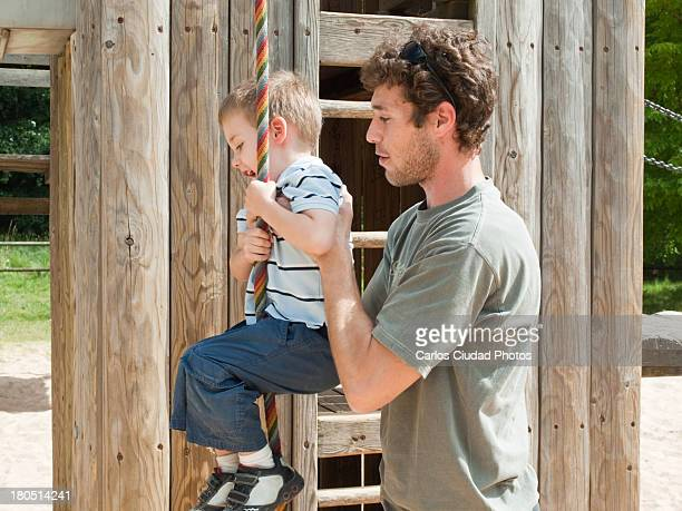 Father helping son to climb a rope
