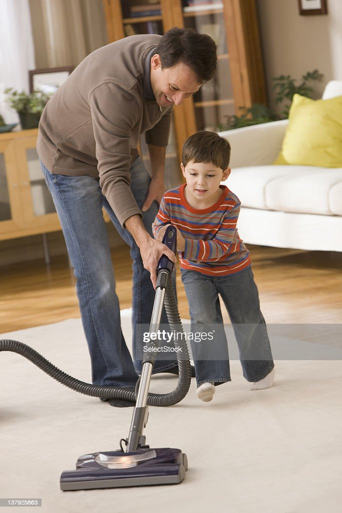 Father helping son to vacuum : Stock Photo