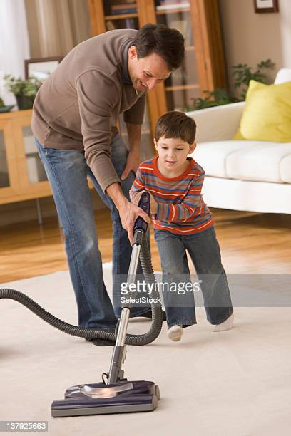 Father helping son to vacuum