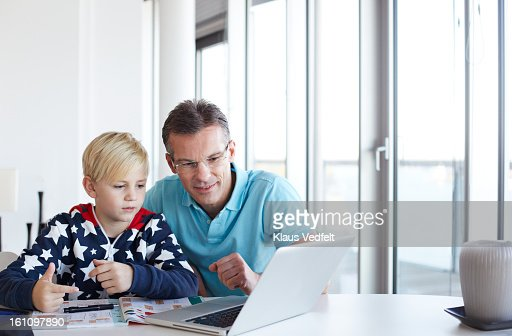 Father helping son with homework : Stock Photo